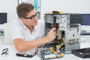Young technician working on broken computer